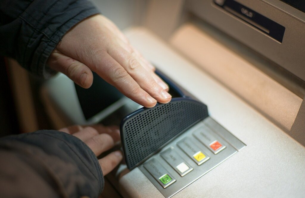 Man covering pin code at an ATM
