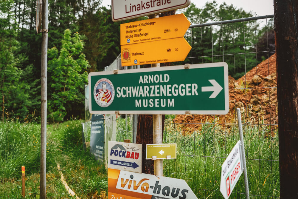 Street signs leading to the Arnold Schwarzenegger Museum in Thal, Austria
