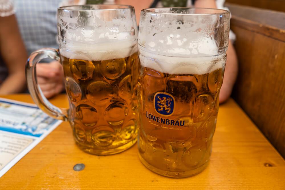 1L Löwenbräu beers on a wooden table at Oktoberfest.