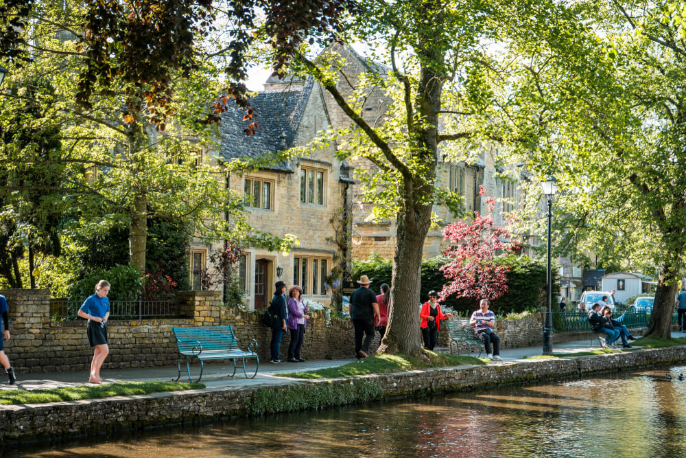 A photo of tourists relaxing by the water in Bourton on the Water in England.