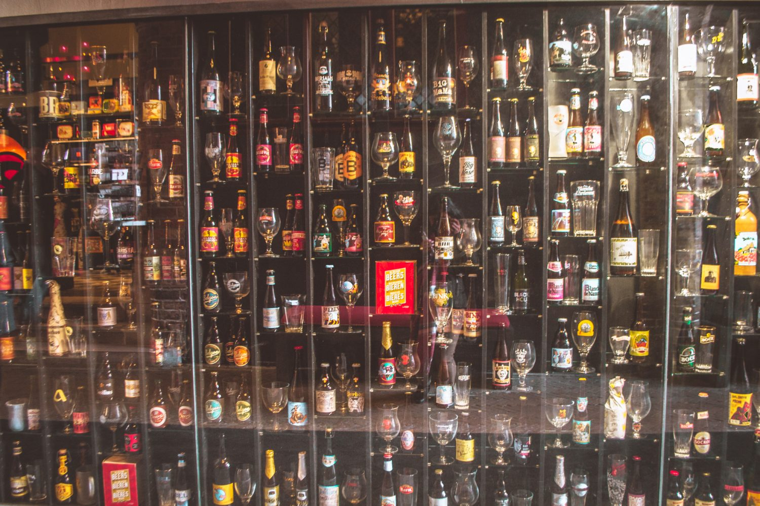 Wall full of different beers and beer glasses in Bruges, Belgium