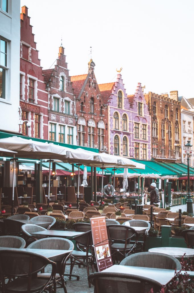 Market Square in Bruges with empty terraces at sunrise