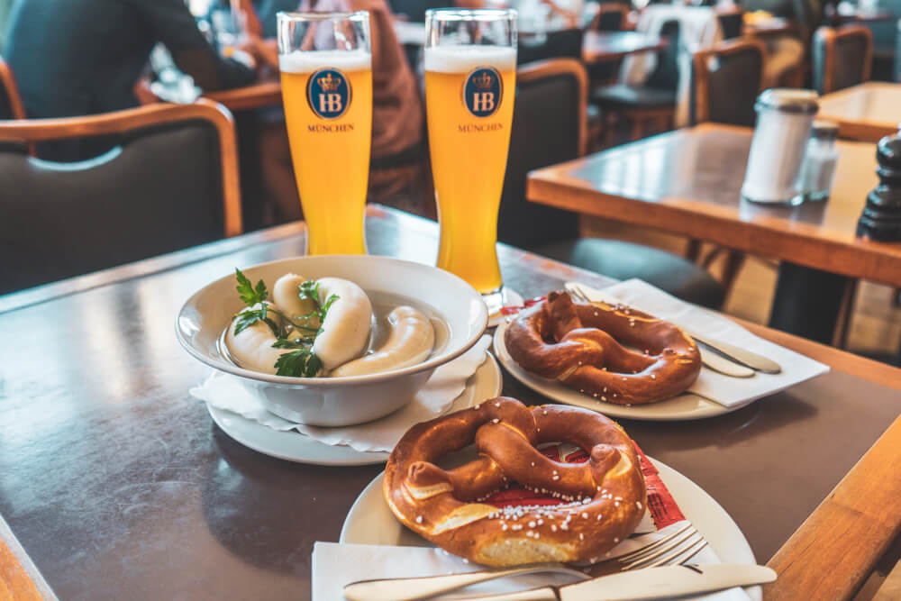 Traditional Bavarian breakfast consisting of white sausages, pretzels and wheat beer.