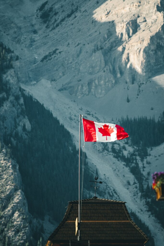 Canadian flag with mountains in the background