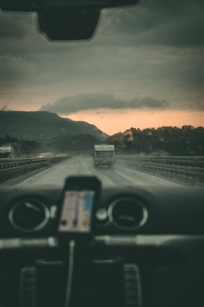 Car with GPS on driving on road at sunset