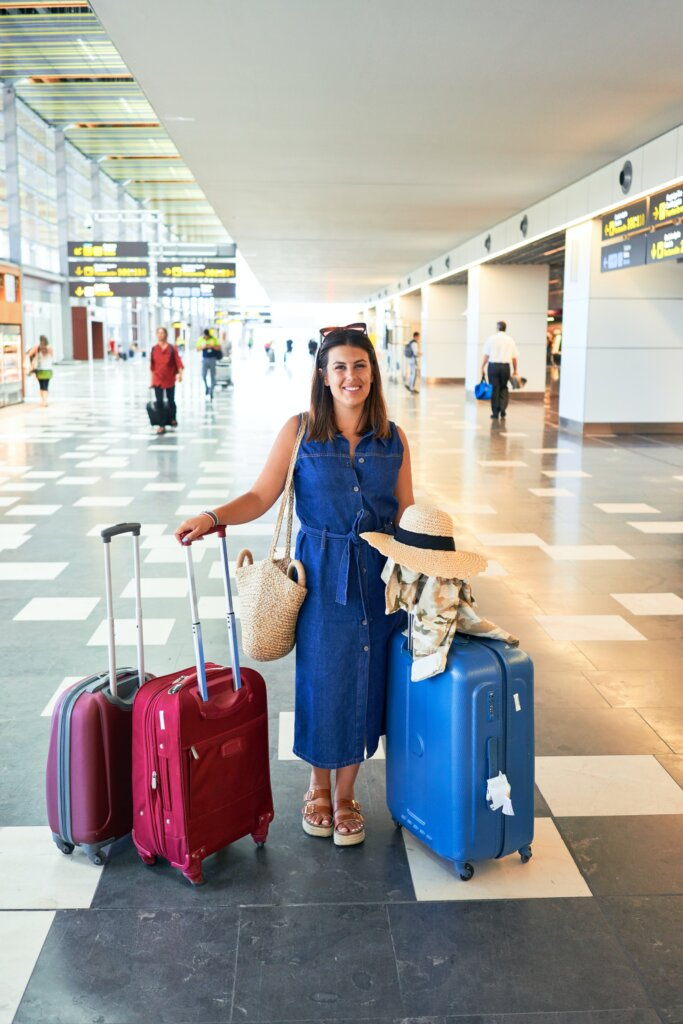 Woman in an airport with three suitcases around her
