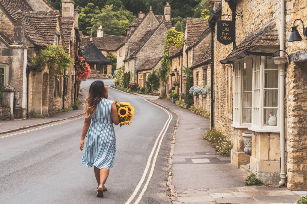 Travel blogger Christina Guan from Happy to Wander walking along the main street of Castle Combe, England.