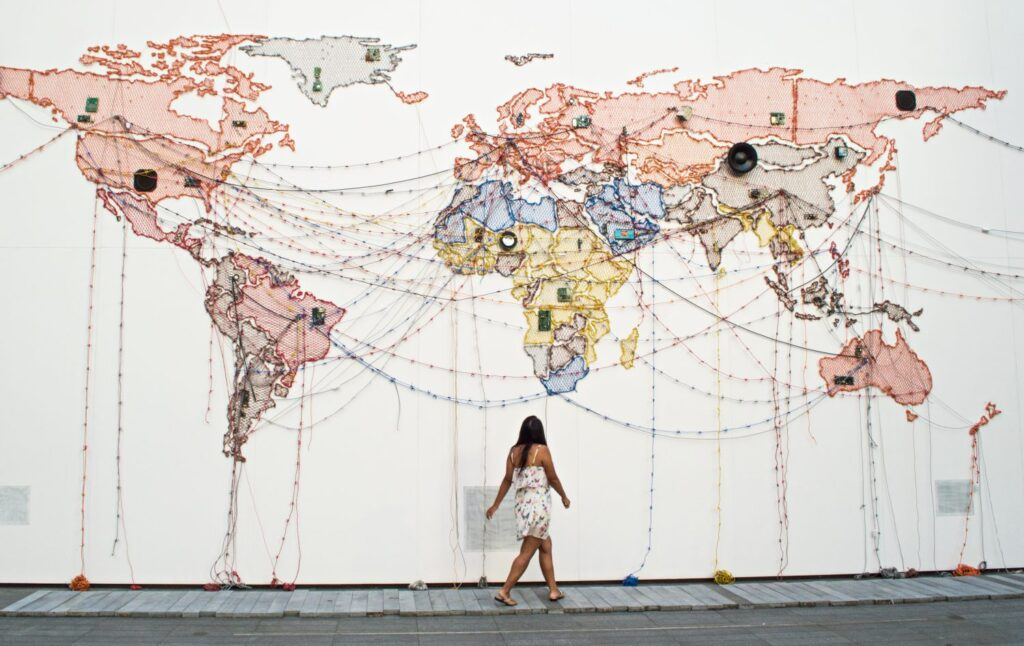 Girl walking in front of a world map installation