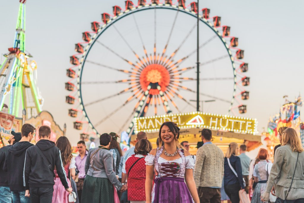 Christina Guan wearing a custom dirndl in front of the ferris wheel at Oktoberfest in Munich, Germany