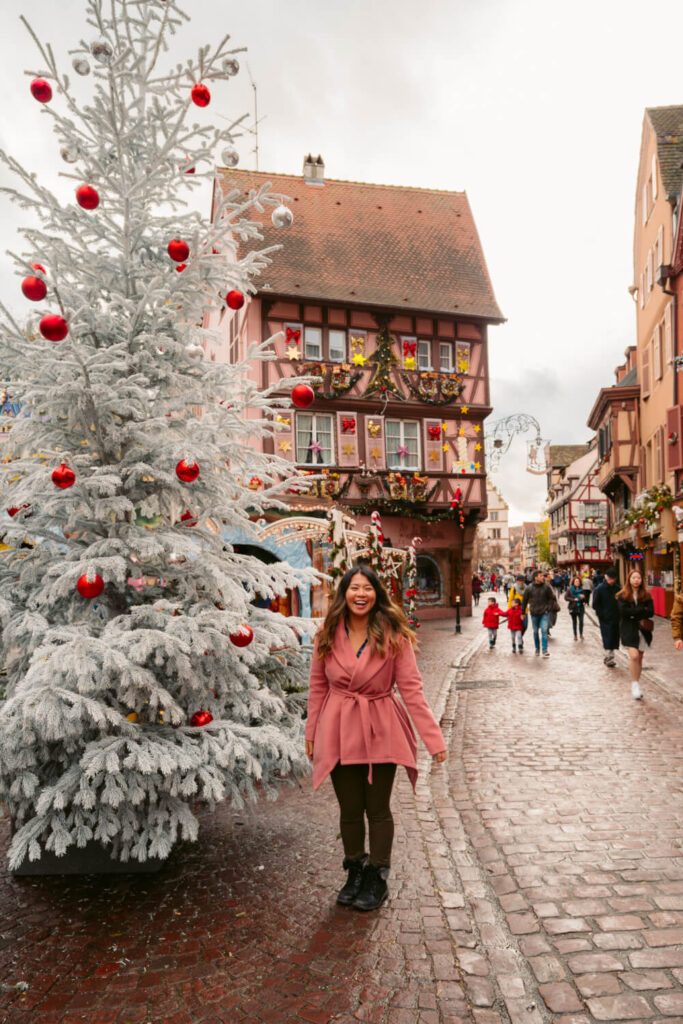 Travel blogger in pink coat posing in front of a white Christmas tree in Colmar, France