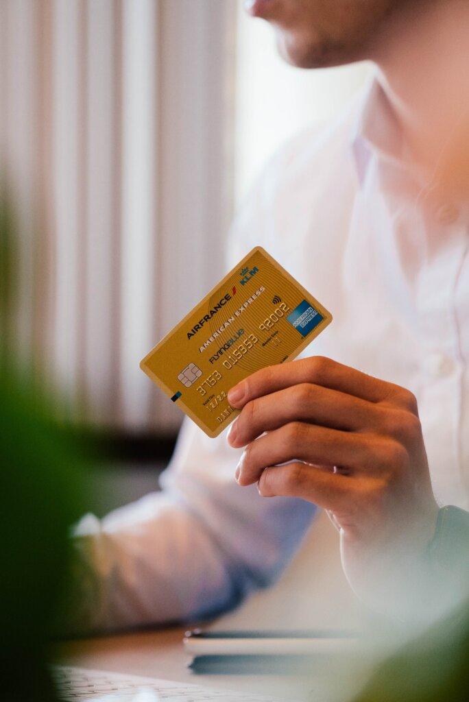 Man holding credit card at computer