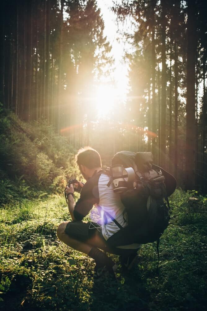 Backpacking man in forest taking a photo