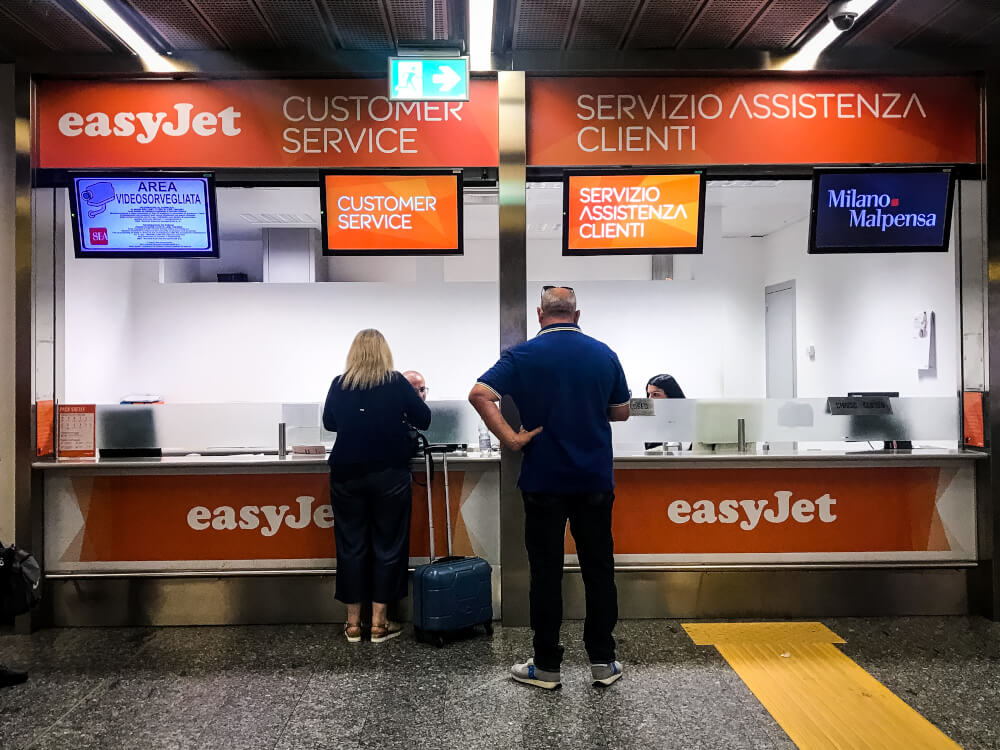 Two passengers standing at an easyJet customer service desk in Milan Malpensa airport