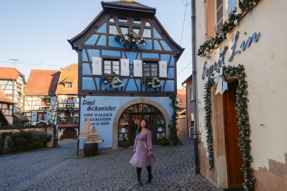 Travel blogger in purple dress in front of a blue house in Eguisheim