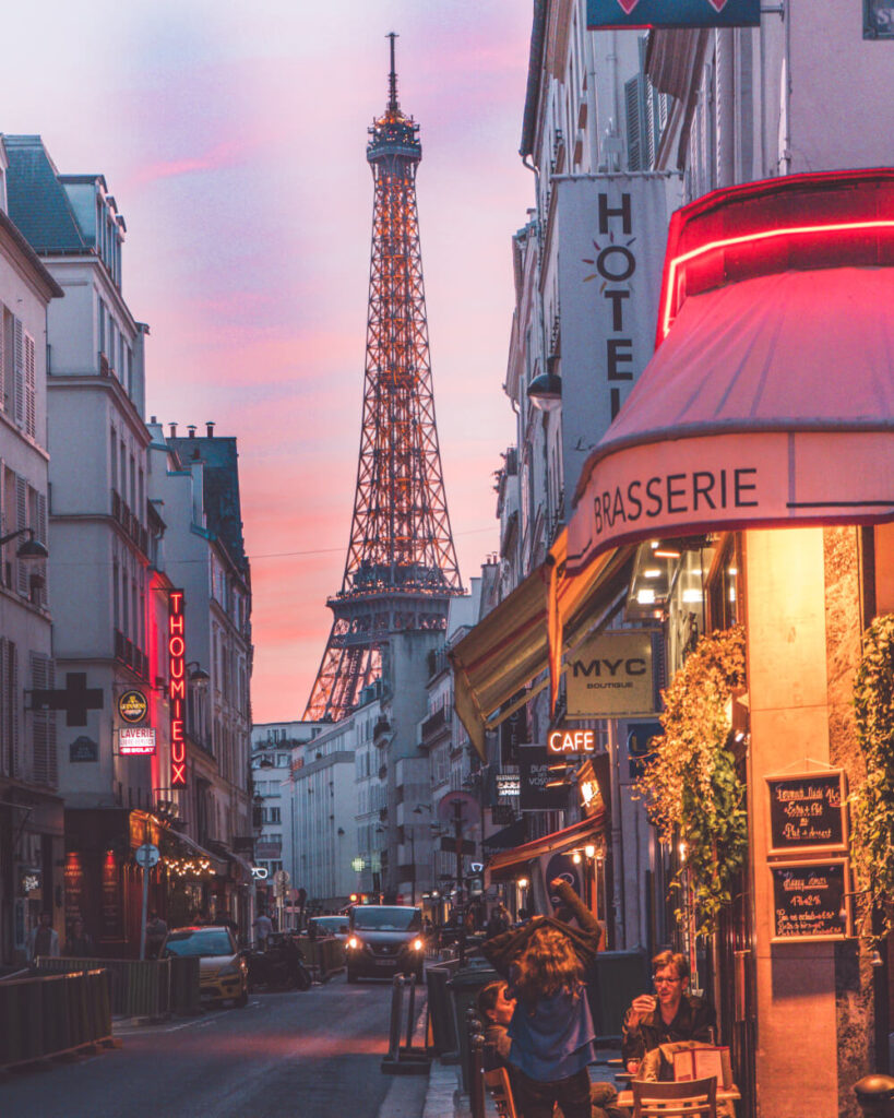Typical Parisian street with the Eiffel Tower in the background with a pink sunset
