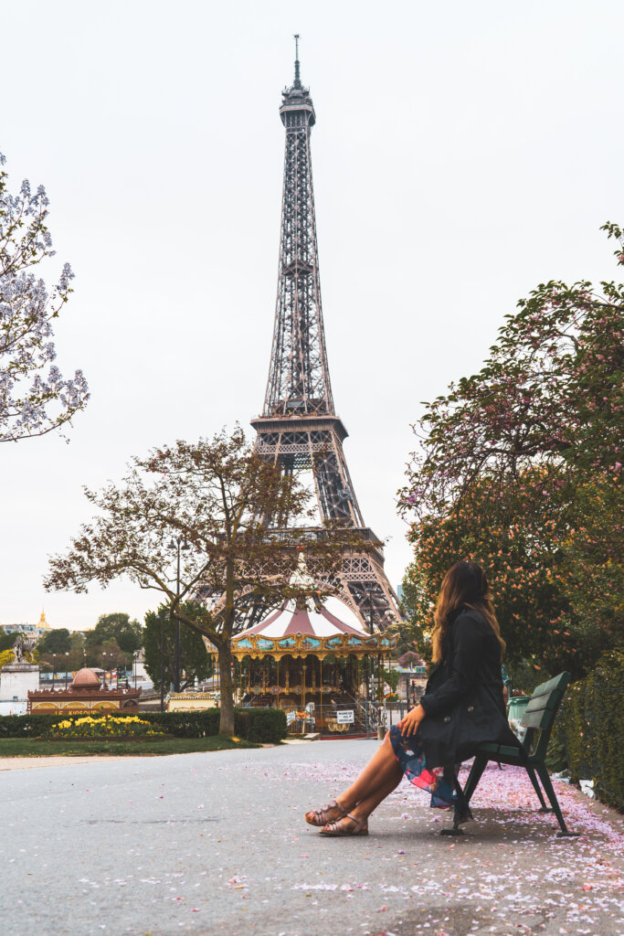 Travel blogger sitting on a bench by the Eiffel Tower