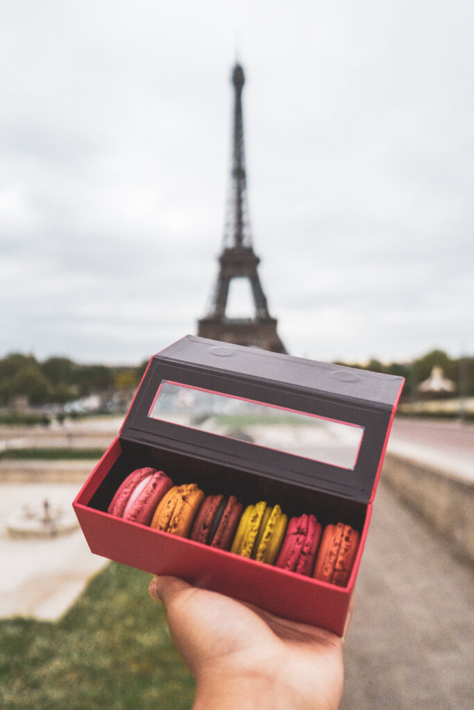 Colourful macarons held out in front of the Eiffel Tower