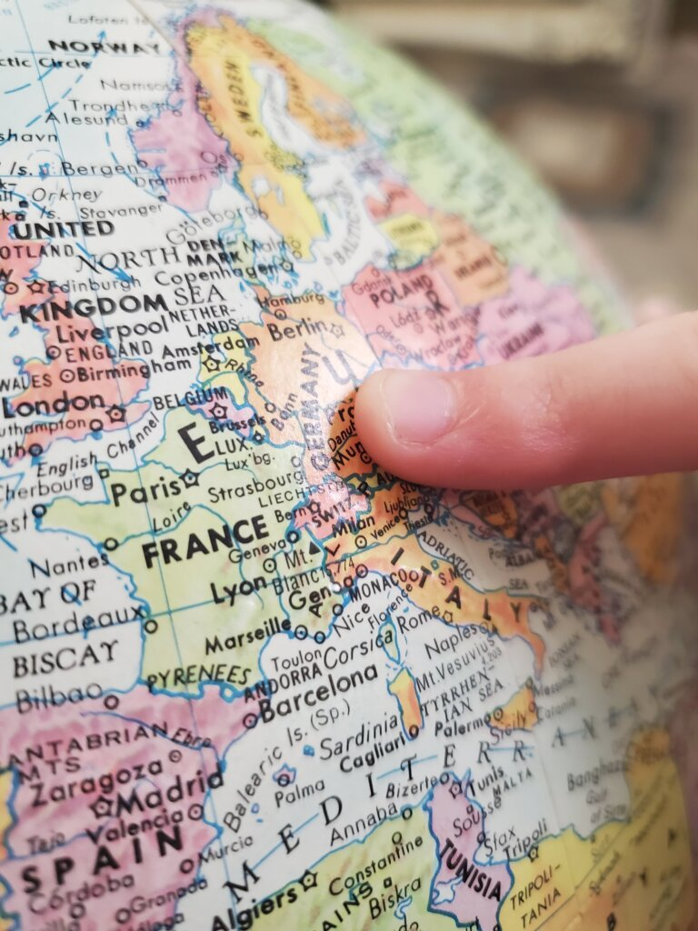 Close up of globe with finger pointing to Europe