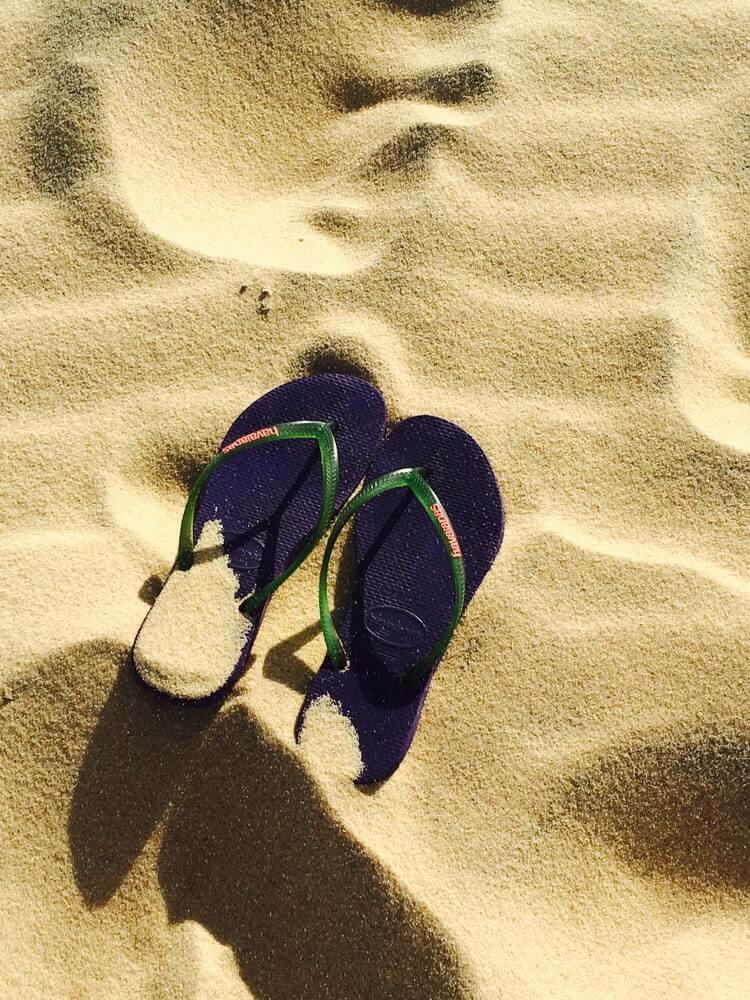 Navy blue flip flops in the sand