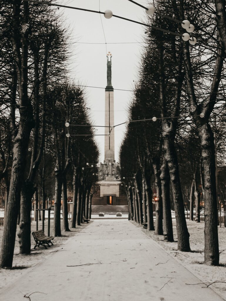Freedom monument in Riga behind snowy trees