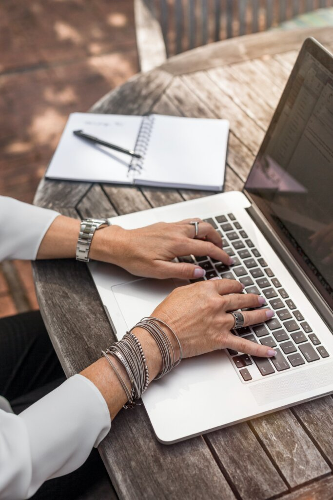 Woman with bracelets and rings typing on a laptop