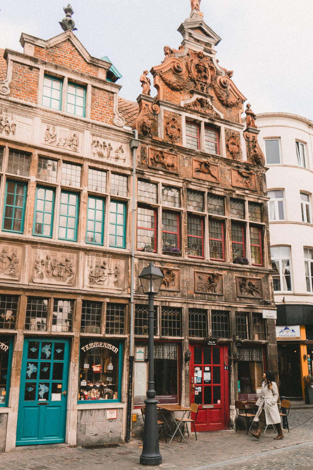 Travel blogger walking in front of beautiful storefronts in Ghent