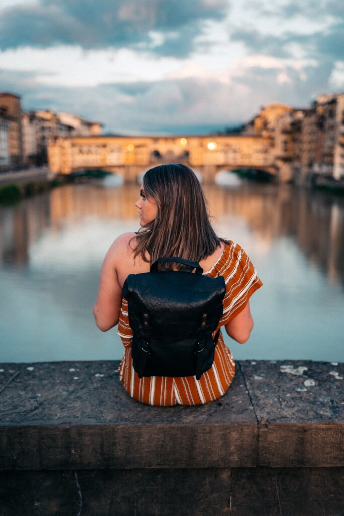 Girl in an orange dress and black backpack sitting at a scenic view in Florence