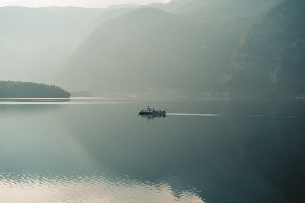 A boat gliding across the lake at Hallstatt, Austria in the early hours of the morning.