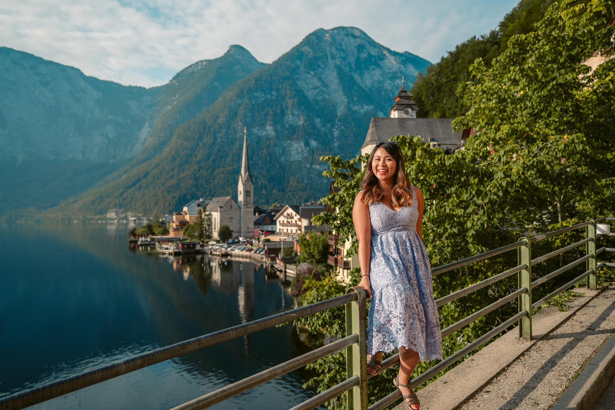 Iconic postcard view of Hallstatt, Austria featuring travel blogger Christina Guan from Happy to Wander.