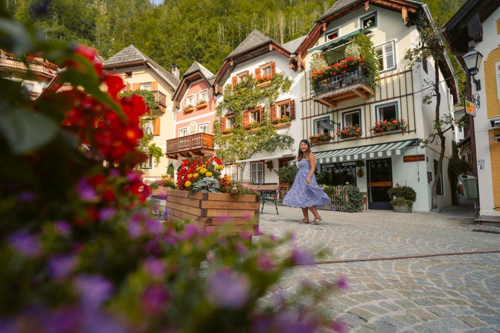 Christina Guan from Happy to Wander in a purple dress enjoying Marktplatz in Hallstatt, Austria.
