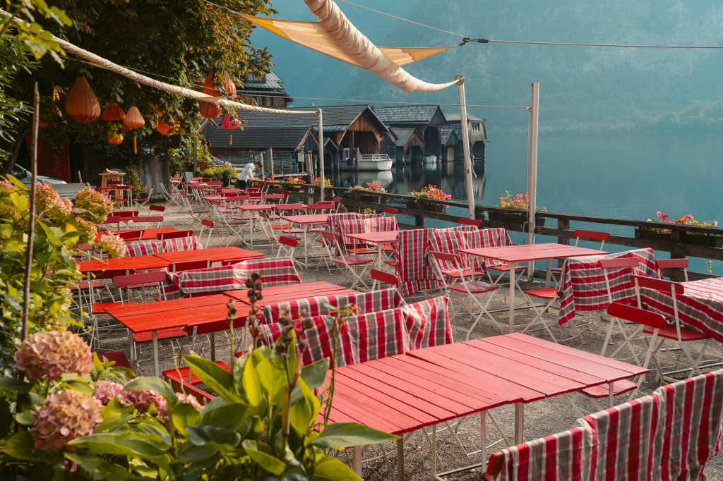 Pretty seating area along the water in Hallstatt, Austria belonging to the Bräugasthof.