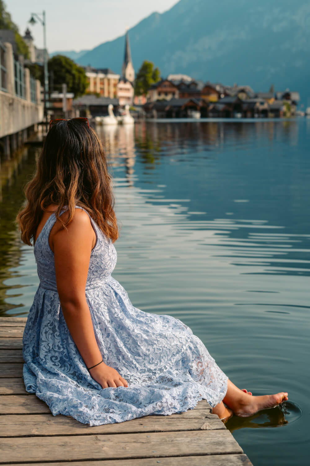 Travel blogger Christina Guan from Happy to Wander by the lake in Hallstatt, Austria.