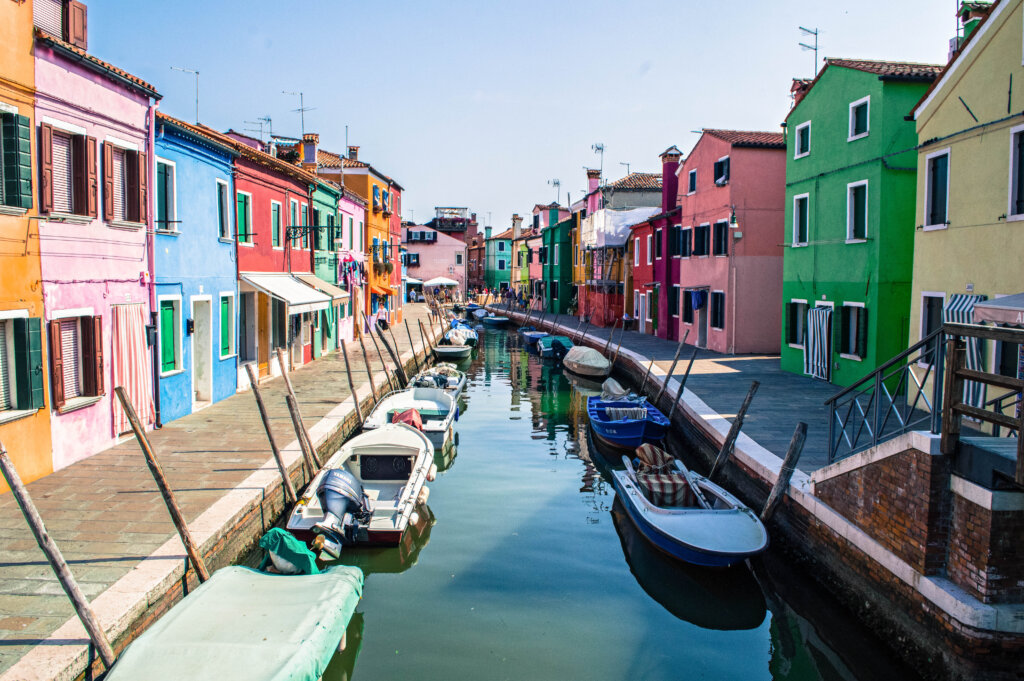 Rainbow houses lining a canal in Burano, Italy