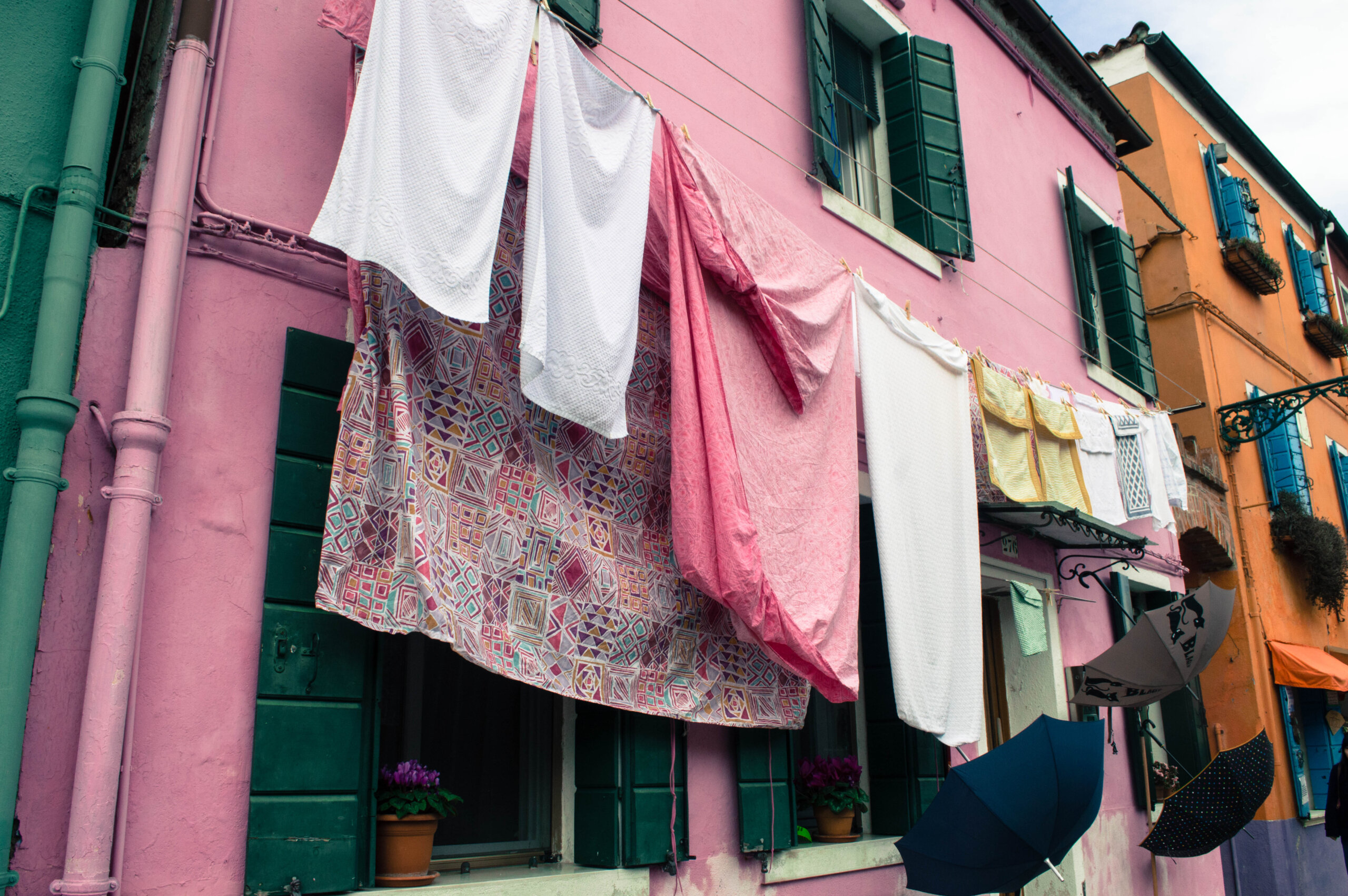 Laundry and umbrellas hanging in Burano Italy
