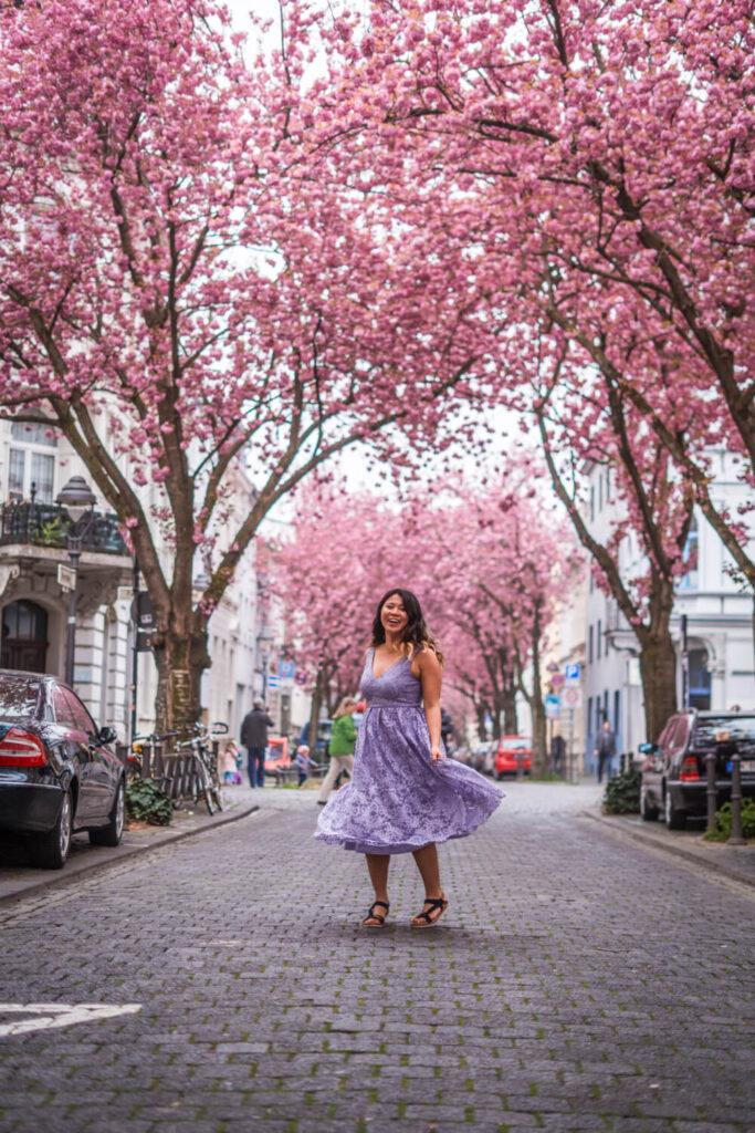 Girl in purple dress twirling on a cherry blossom filled street in Bonn, Germany