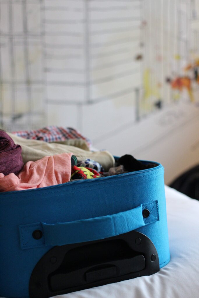 Blue suitcase filled with clothing on a bed