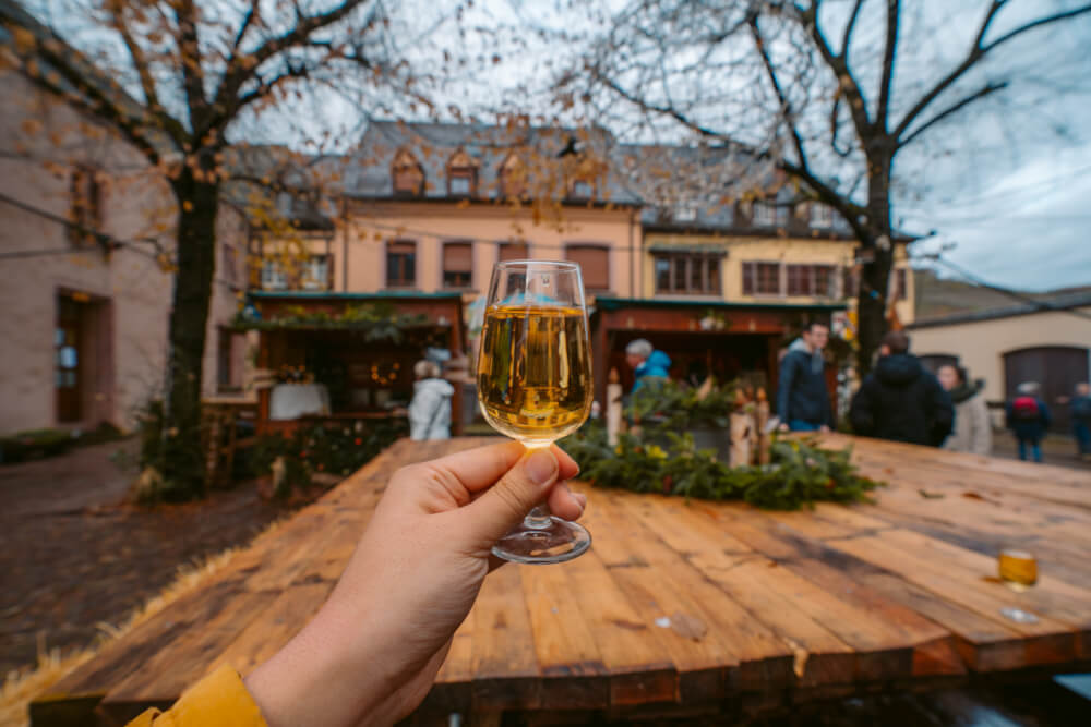 Glass of wine held out at a Christmas market in Kaysersberg, France