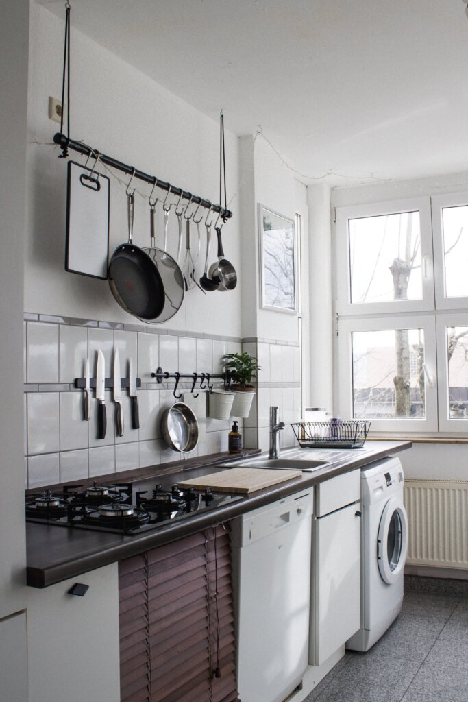 Apartment kitchen with pots on the wall and a laundry machine