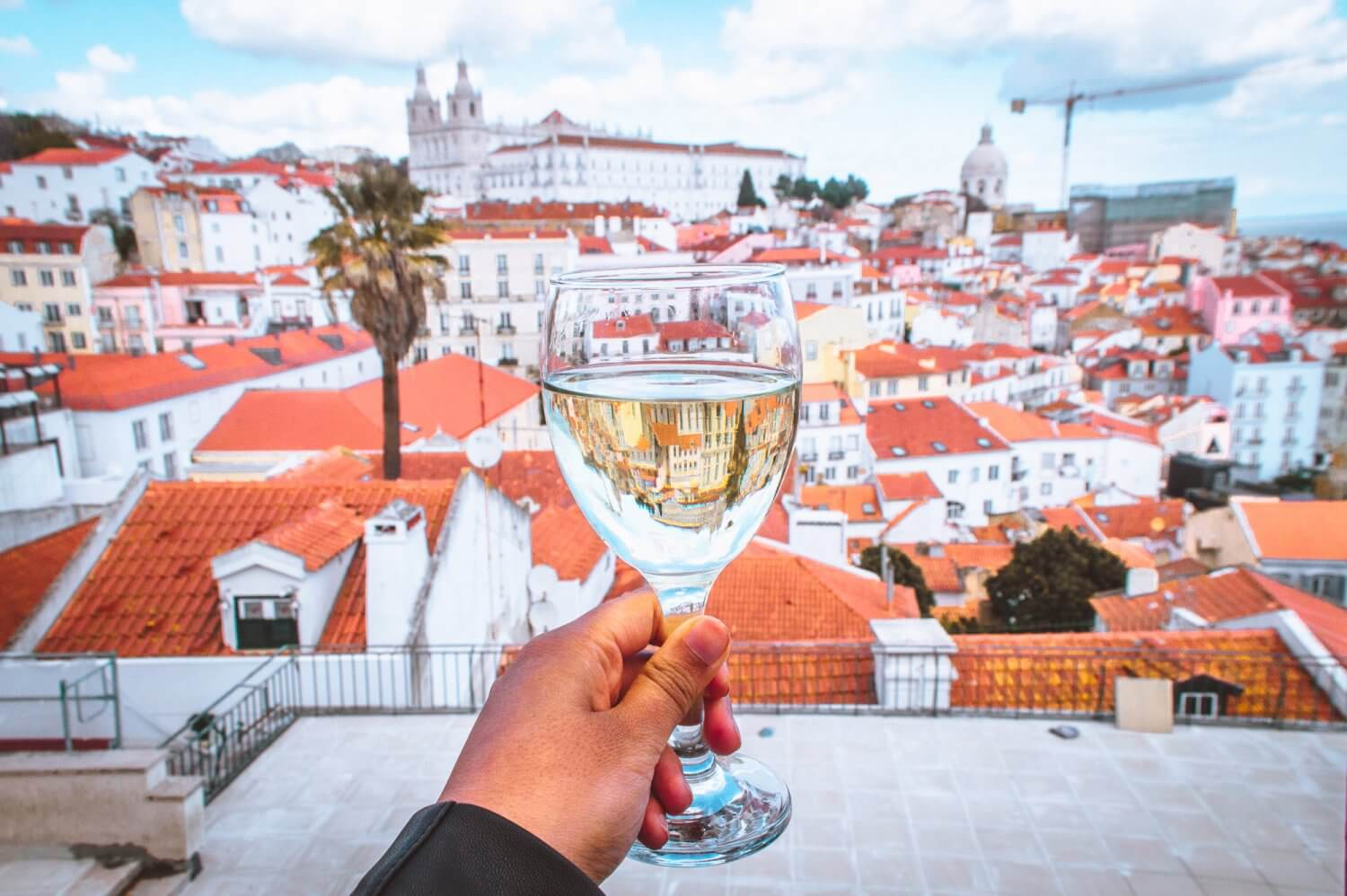 A glass of wine overlooking beautiful Lisbon from Bar Terraco de Santa Luzia, a must when you visit Lisbon.
