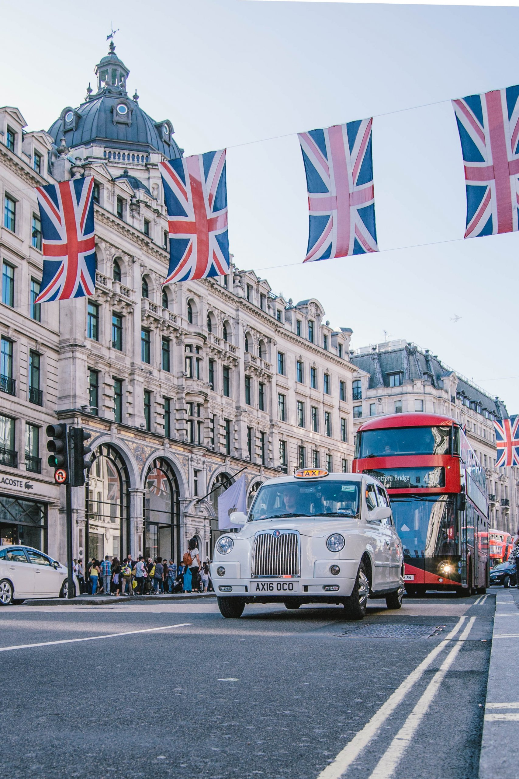 British flags in London with cars and buses on the road