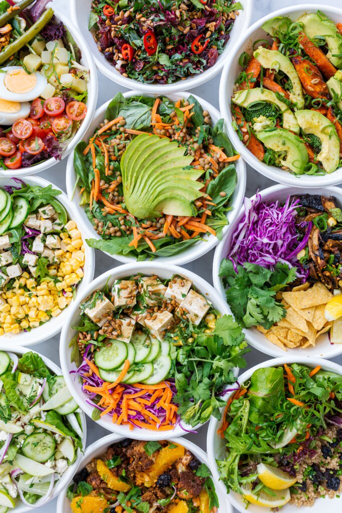 Colourful salads in lunch containers on a table