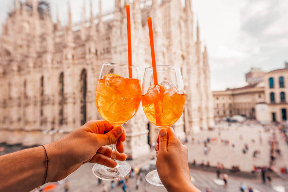 Aperol spritz cheersing in front of the Duomo in Milan