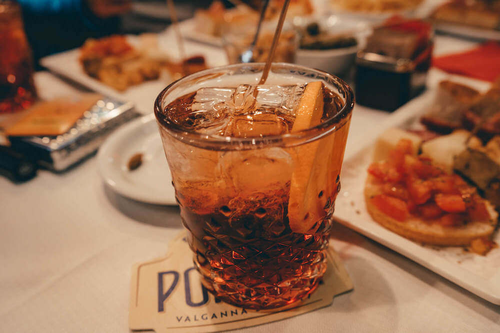 A cold Negroni with plates of delicious food