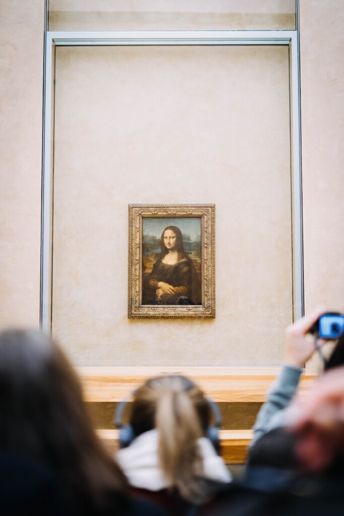 Tourists photographing the Mona Lisa at the Louvre Museum in Paris, France