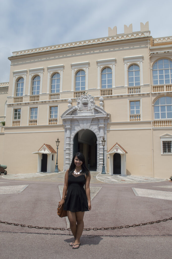 Girl posing in front of Monaco royal palace in a black dress