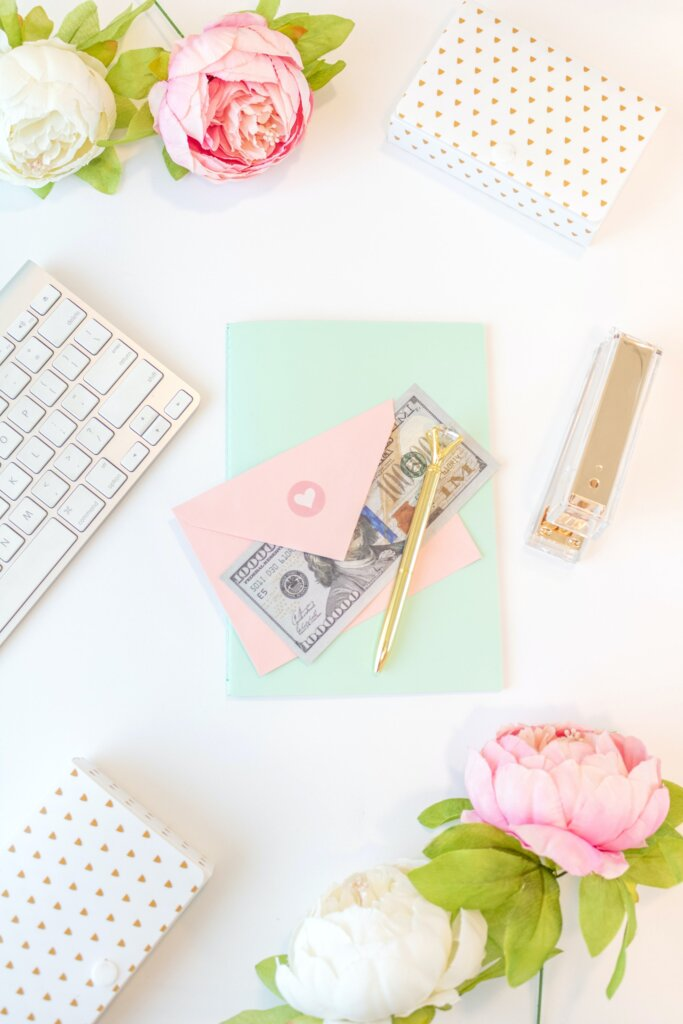 Flat lay with money, envelopes, flowers and a keyboard on a white desk