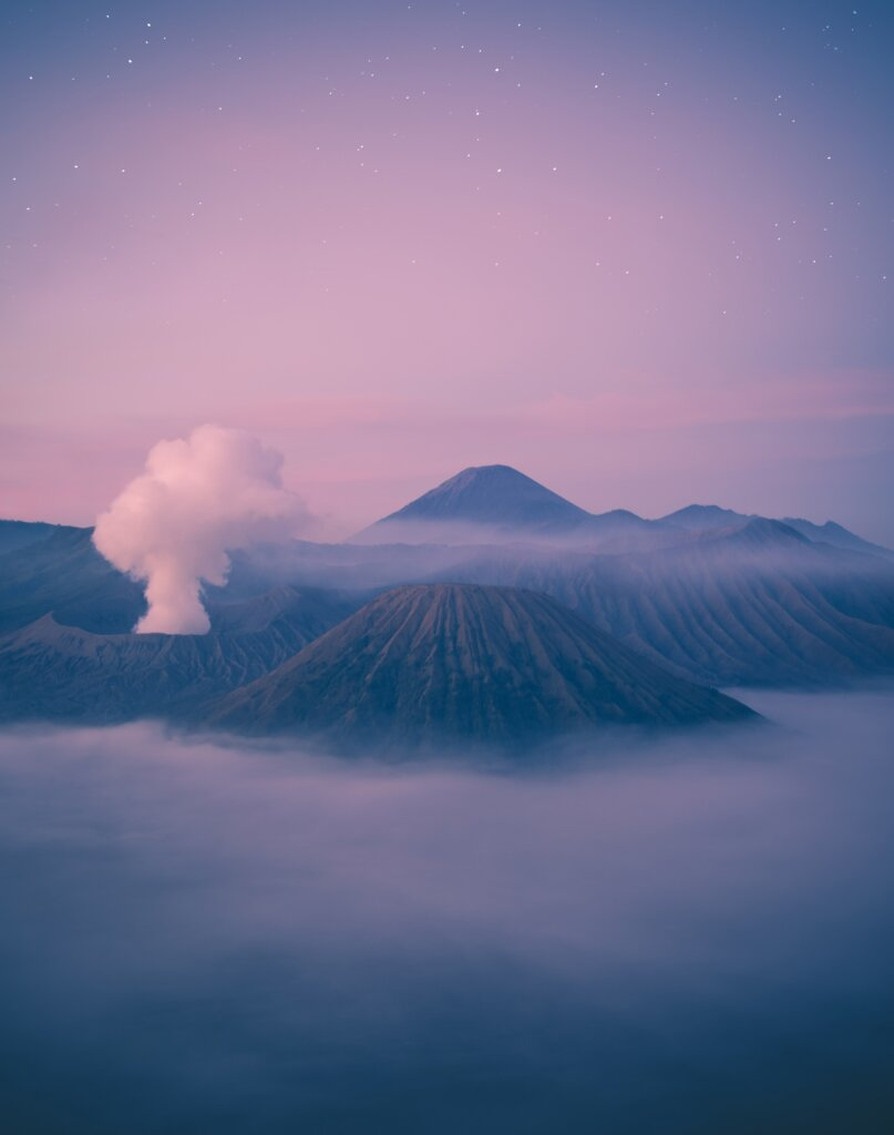 Pink sunrise views over foggy Mount Bromo in Indonesia