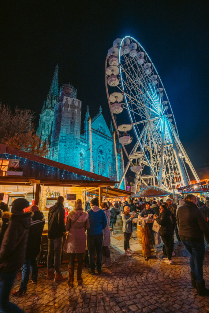 Ferris wheel and cathedral at Mulhouse Christmas Market in France