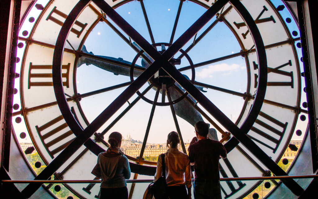 Tourists admiring the clock face in the orsay Museum of Paris, France