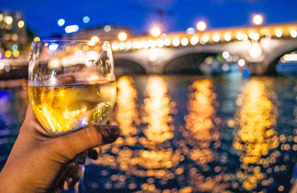 Glass of white wine being held out in front of the Seine River
